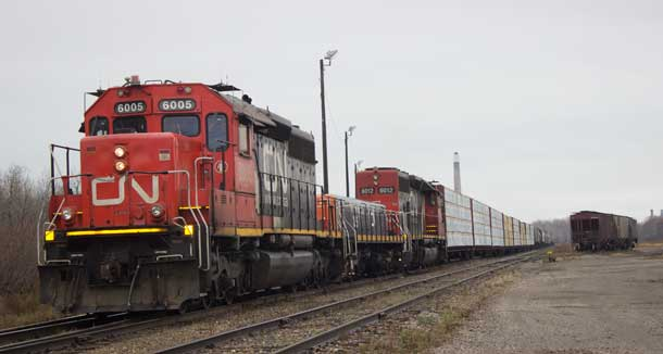 CN Train loaded with lumber stuck on the south side of the tracks.