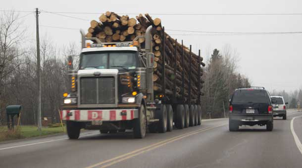 Logging truck loaded with logs headed to saw mill.