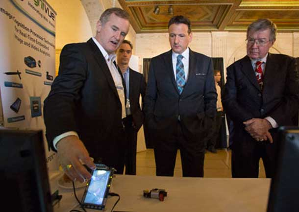 Minister of State for Science and Technology Greg Rickford and NRC President John McDougall watch a demonstration of an innovative technology developed by NRC-IRAP client Cognivue.
