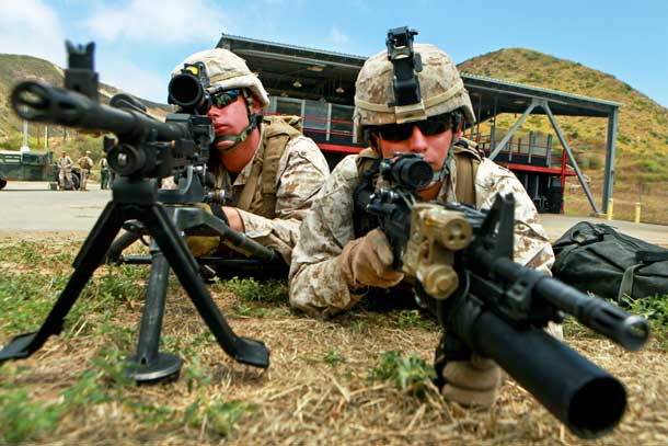 Marine Corps Lance Cpls. Benjamin V. Stout assists Lance Cpl. Josh M. Tasior as they hold security on the outer cordon of a target site during a Maritime Raid Force training course on Camp Pendleton, Calif., Jun. 15, 2011. Stout and Tasior are machine gunners assigned to the 11th Marine Expeditionary Unit's maritime raid force. U.S. Marine Corps photo by Cpl. Chad J. Pulliam