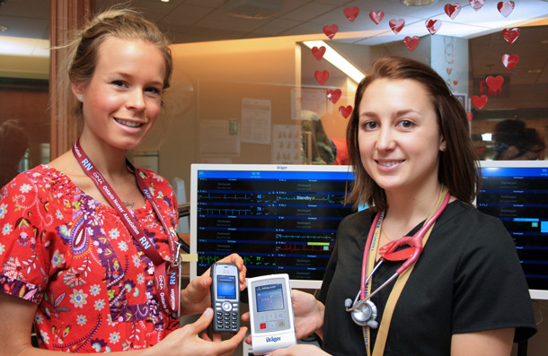 Robyn Mauro (right) holds the portable telemetry unit, which allows patients to be monitored away from their beds. Information appears on the screens (background) at the nurses' station. Riley Burgsteden shows a special phone that alerts nurses on rounds if there is a problem with a patient.