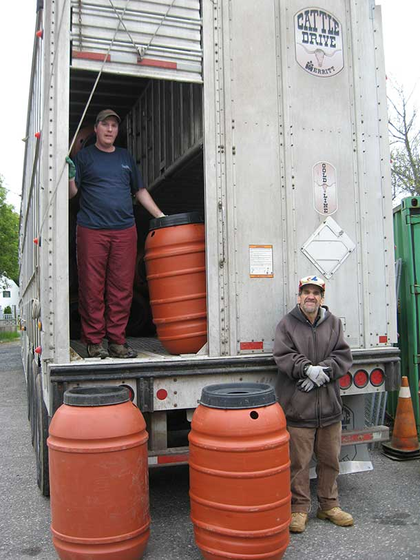 """Murray and Justin from the Monte Parks Centre Employment Opportunities program unload a truck full of rain barrels for EcoSuperior. """"It's one non-profit organization helping another,"""" says EcoSuperior executive director Ellen Mortfield. """"The Monte Parks folks are a great resource when we need some help."""""""