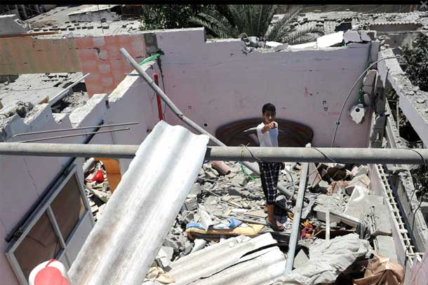 A young boy stands in the ruins of a house which was destroyed during an air strike in Central Bureij refugee camp in the Gaza Strip. Photo: UNRWA