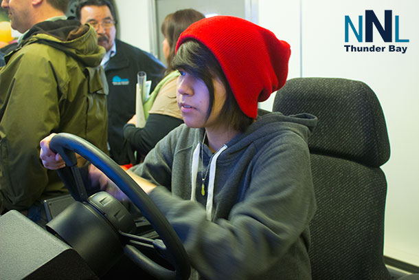 At the Nuna Teaching Technology trailer, Jessica tries her skill at driving the Cat 777 Simulator.