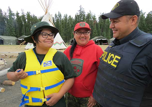 ior Canadian Ranger Autumn Sutherland of Fort Albany tries on one of the life jackets donated by OPP Sergeant Marty Singleton, while Ranger Jessie Sutherland, centre, looks on.