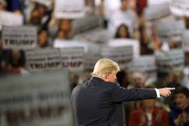 Republican presidential candidate Donald Trump points out a questioner at a campaign rally at the Iowa State Fairgrounds in Des Moines, Iowa, December 11, 2015. REUTERS/Scott Morgan