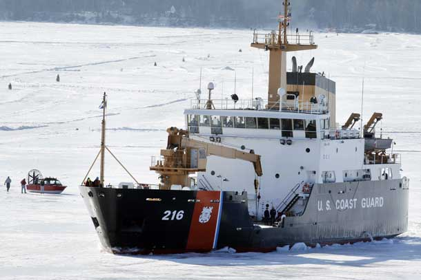 STANDALONE PHOTO -- The U.S. Coast Guard cutter Alder breaks ice near a windsled Wednesday, April 3, 2013 near the harbor in Bayfield, Wis. on Lake Superior. The Madeline Island ferry plans to resume running on Friday. Most traffic across Lake Superior between Bayfield and Madeline Island is either via the ferry or, in the depths of winter, the ice road. But when the ice is either breaking up or settling into its winter thickness, people can get across only by the wind sled - an enclosed boat-hulled craft with huge fans on the back that push the vehicle across the shifting ice.. The wind sleds are usually in action for 10 to 14 days at the beginning of winter and about a week in the spring, though the duration varies each year. MARK HOFFMAN/MHOFFMAN@JOURNALSENTINEL.COM