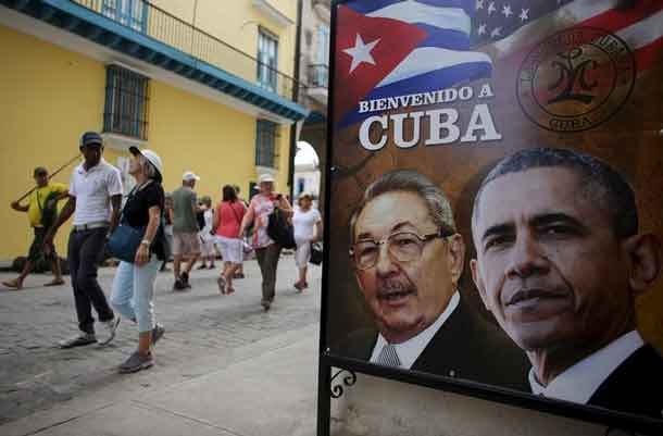 Tourists pass by images of U.S. President Barack Obama and Cuban President Raul Castro in a banner that reads