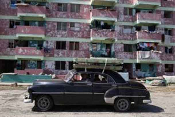 People transport beds on the roof of a vintage car in Baracoa. REUTERS/Alexandre Meneghini