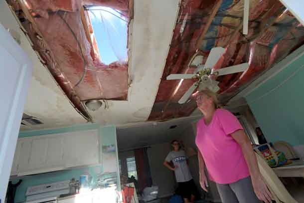 Diane Blumling (R) looks at a hole in the roof of her home while removing belongings in the aftermath of Hurricane Matthew at the Surfside Estates neighborhood in Beverly Beach, Florida, U.S., October 8, 2016. REUTERS/Phelan Ebenhack