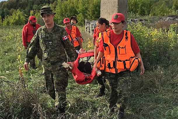 Canadian Rangers carry Sergeant Mary Miles on an improvised stretcher after she broke an ankle during a search and rescue exercise. credit: Warrant Officer Borton, Canadian Rangers