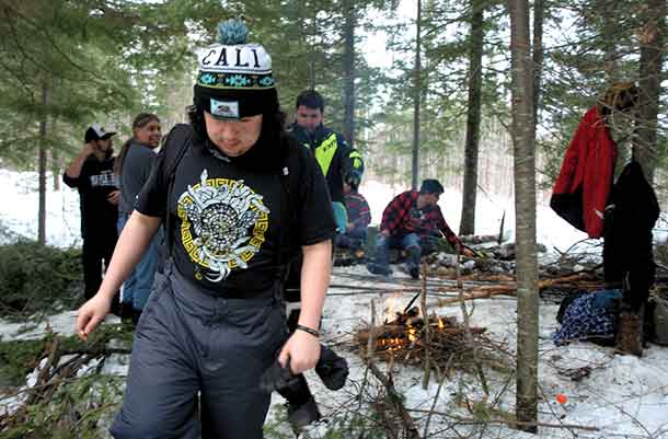 LEARNING TO SURVIVE in the winter on the land was provided to Wabun Youth during a week long youth gathering near Timmins. Pictured in the foreground is Max Worme, of Mattagami FN heading to get wood for the fire.
