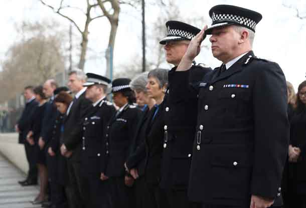 Police officers salute during a minute's silence outside New Scotland Yard. REUTERS/Neil Hall