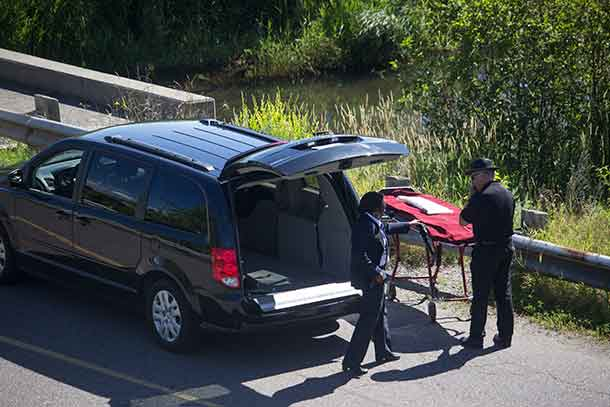 Attendants from funeral home getting set to remove body from near the mouth of McVicar's Creek