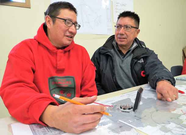 Ranger Jeffery Fiddler of Muskrat Dam, left, gives his brother, Grand Chief Alvin Fiddler of Nishnawbe Aski Nation, a briefing during a search and rescue exercise in Sachigo Lake in 2015.