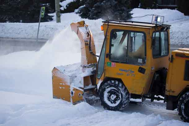 City of Thunder Bay using a snowblower to clear sidewalks of the last storm