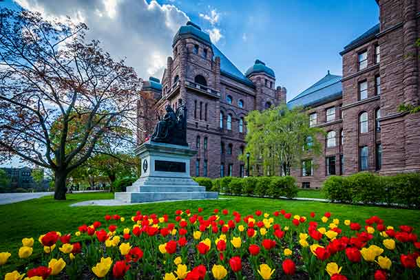 Tulips and statue outside the Legislative Assembly of Ontario, in Toronto, Ontario as the race to the June election heats up. Image Depositphotos.com