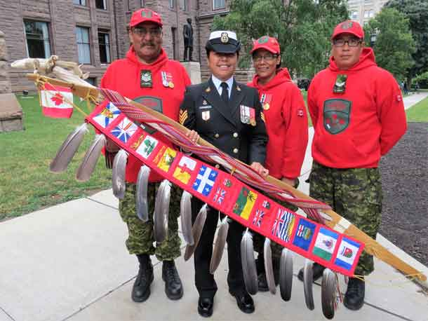 Sergeant Charlie Linklater, left, Master Corporal Emily Beardy, centre, and Corporal Terrence Duncan, right, with the Canadian Armed Forces eagle staff and its bearer.