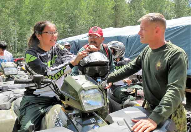 Sergeant Kevin Meikle goes over the parts of an ATV with a Junior Canadian Ranger.