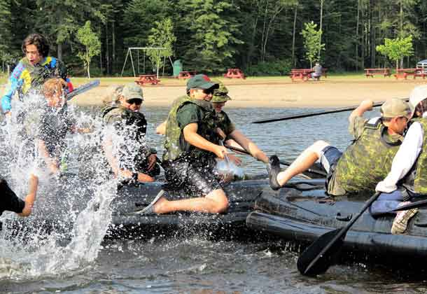 Junior Canadian Ranger Reilly Thivierge, centre, gets into a water fight while training on an assault boat.