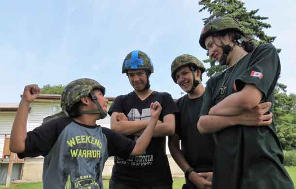 Briere Morriseau,10, of Thunder Bay, left, shows his muscles to Junior Canadian Rangers ReillyThivierge, 14, Dylan Chisel, 16, and Terrance Angeconeb, 13, of Lac Seul First Nation.
