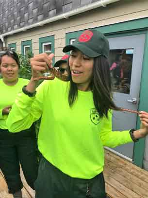 Junior Ranger Chasity Koosees of Kashechewan handles a snake for the first time at the Newfoundland Insecterium.