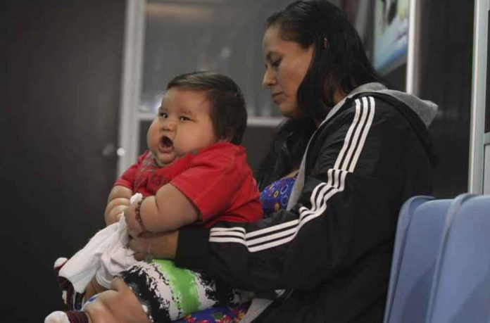 ARCHIVE PHOTO: Eight-month-old Santiago Mendoza waits with his mother Eunice Fandino at a clinic for the obese in Bogota March 19, 2014. REUTERS/John Vizcaino