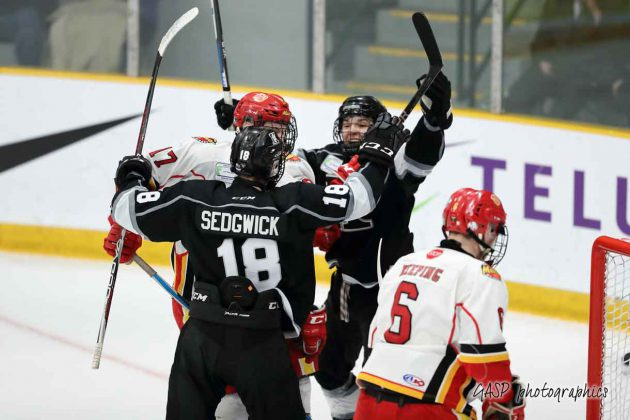 Macs Cameron Brown gets caught up in the middle of Mackenzie Sedgwick and Trenton Morriseau's tying goal celebration by the Kings