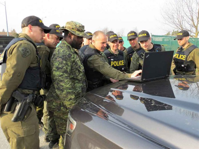 Sergeant Eric Scott and OPP officers look at a computer map of an area to be searched.