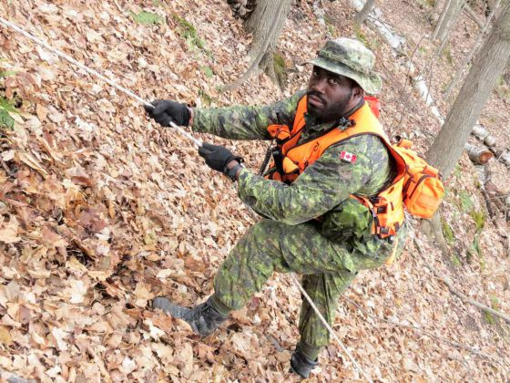 Sergeant Eric Scott uses a rope to climb a steep incline during a search exercise.