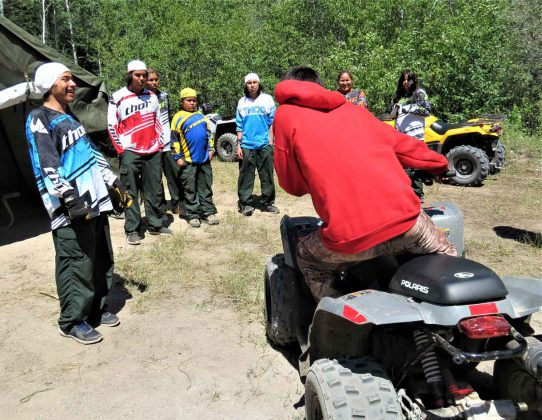 A Canadian Ranger shows Junior Canadian Ranger how to use their body weight to keep an ATV stable. Photo by Sgt Peter Moon Canadian Rangers