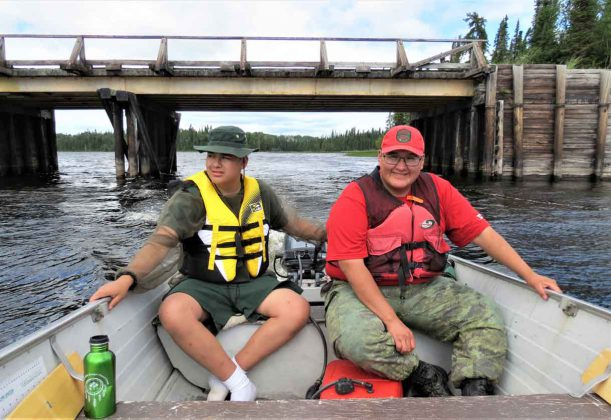 Junior Canadian Ranger Daniel Bottle, left, drives a safety boat with Corporal Ralph Winter of Wapekeke during boating training for Junior Rangers at Camp Loon.