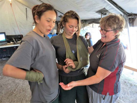 Nancy Hutchinson, right, a St. John Ambulance first aid instructor, teaches two Junior Canadian Rangers how to make a sling. Photo credit Sergeant Peter Moon, Canadian Rangers