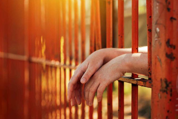 Female hands behind prison yard bars