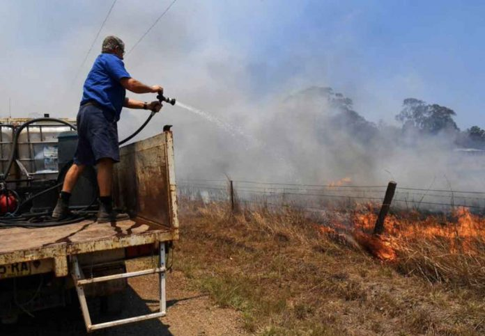 Tinonee resident Brian Acheson sets up his tip truck as a makeshift fire truck to assist residents fighting spot and grass fires in the Hillville area near Taree, NSW, Australia, November 13, 2019. AAP Image/Dean Lewins/via REUTERS