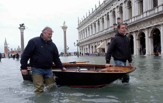 Citizen with a boat walk in St. Mark's Square after days of severe flooding in Venice, Italy, November 17, 2019. REUTERS/Manuel Silvestri