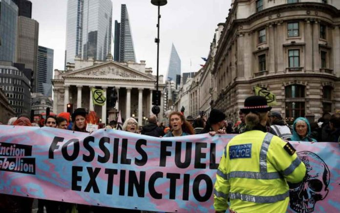 Protesters shout slogans as they block the road during an Extinction Rebellion demonstration at Bank, in the City of London, Britain October 14, 2019. REUTERS/Henry Nicholls