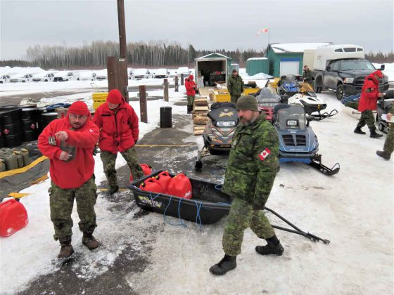 Rangers fuel snowmobiles and load supplies for the departure of troops for on-the-land training.
