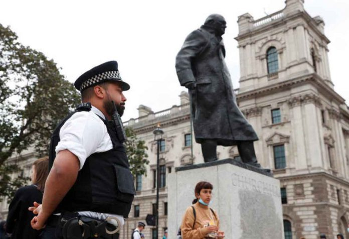 A police officer stands next to the statue of Winston Churchill at Parliament Square which was damaged by protesters with graffiti, in the aftermath of protests against the death of George Floyd who died in police custody in Minneapolis, London, Britain, June 8, 2020. REUTERS/John Sibley