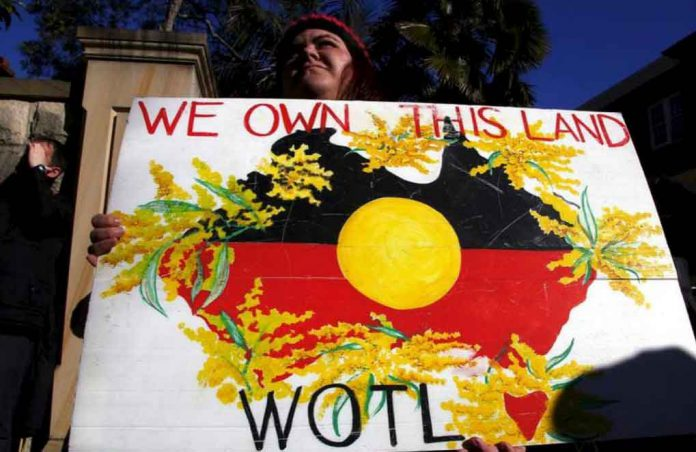 FILE PHOTO - A protester holds a placard as she stands outside the venue for a meeting between Australia's Prime Minister Tony Abbott and forty of the nation's most influential Indigenous representatives in Sydney, Australia, July 6, 2015. REUTERS/David Gray