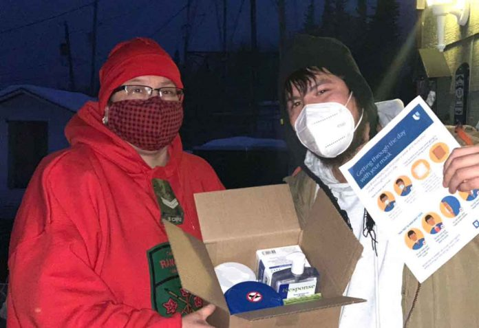 Master Corporal Ruby Edwards-Wheesk, left, shows a box containing personal protective equipment to her son Wendell. The boxes are being distributed to every resident of Fort Albany during the crisis. credit Canadian Rangers