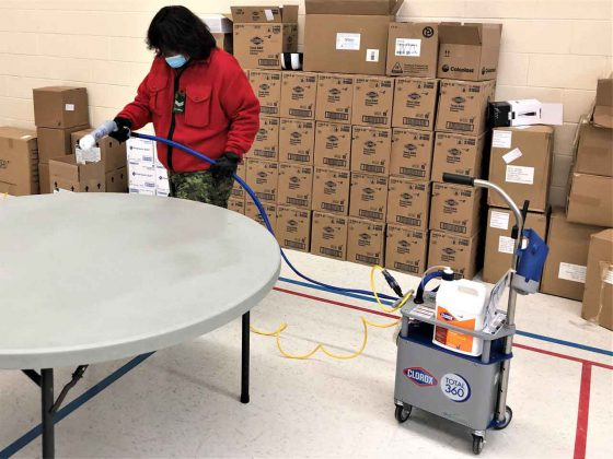 Corporal Reed Finlayson disinfects a surface before packing food boxes for community members living alone in Ginoogaming. credit Warrant Officer Carl Wolfe
