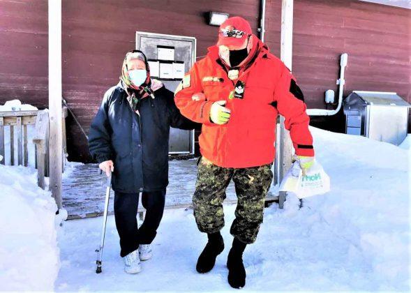 Sergeant Matthew Gull helps Elder Elizabeth Koostachin, 86, getto her Covid shot in Peawanuck credit Master Corporal Pamela Chookomoolin, Canadian Rangers