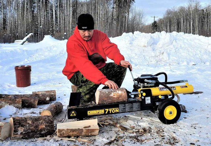Master Corporal Shaun Kakegamic uses a wood splitter to prepare firewood for elders in Muskrat Dam. credit Sergeant Emily Beardy, Canadian Rangers