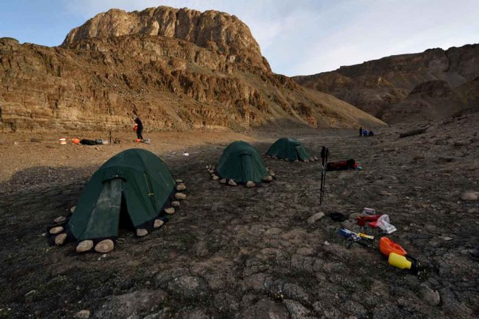 The expedition to Greenland was a challenge: After arriving by plane and boat, the team had to hike for three more days before they could set up their tents beneath the caves they were looking for. CREDIT Robbie Shone