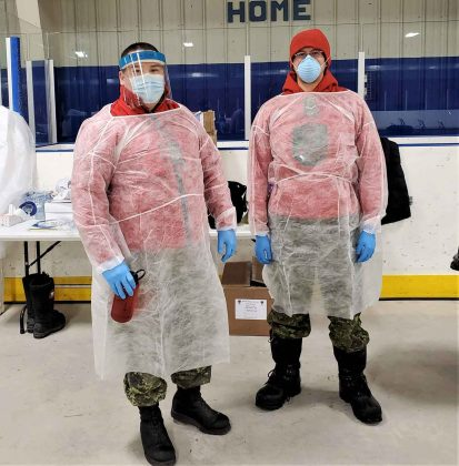 Sergeant Byron Corston and Ranger Nathaniel Keesic wear protective gowns while assisting a medical team delivering COVID-19 vaccinations in Moose Factory. credit Canadian Rangers
