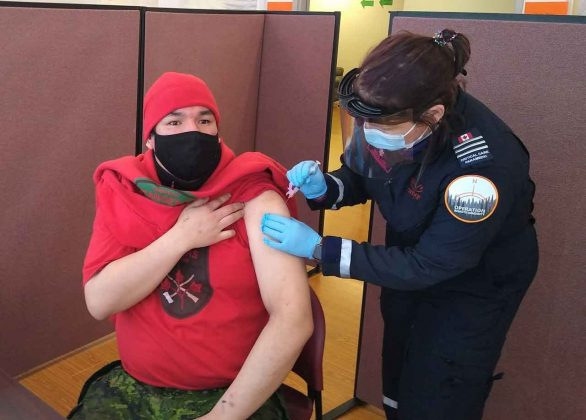 Master Corporal Sinclair Childforever of Fort Severn receives a COVID vaccination while assisting paramedics in the delivery of the vaccine in Sachigo Lake. credit PO2 Kevin McCue