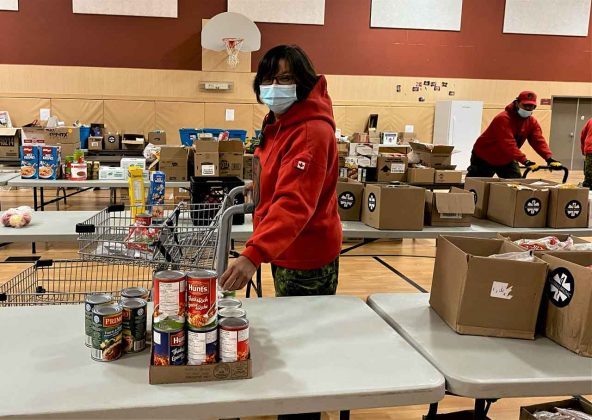 Master Corporal Rita Brisket of Lac Seul packs a food hamper for a family quarantined in its home because of COVID. credit Sergeant Janet Butt, Canadian Army