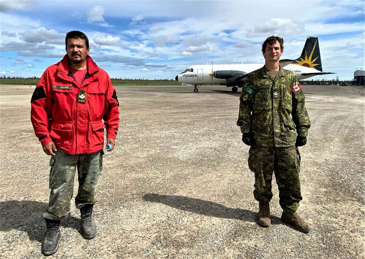 Master Corporal Joe Lazarus of the Canadian Rangers, left, and Master Corporal Jason Lane at the Kashechewan airport. A cargo plane bringing in food and supplies for the residents of the First Nation is behind them. credit Sergeant Janet Butt, Canadian Rangers